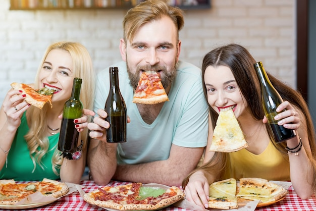 Portret młodych zabawnych przyjaciół ubranych niedbale w kolorowe koszulki trzymających kawałek pizzy i piwa w domu