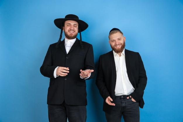 Portret młodzi ortodoksyjni żydowscy mężczyzna odizolowywający na błękitnym studiu