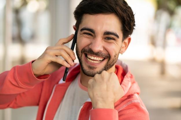 Portret młodzieńca rozmawia przez telefon i świętuje dobre wieści, stojąc na zewnątrz na ulicy