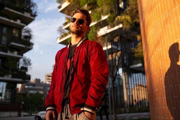 Portret młodzieńca w okularach przeciwsłonecznych i czerwonej kurtce, patrząc pewnie na miasto będące zachodem słońca.