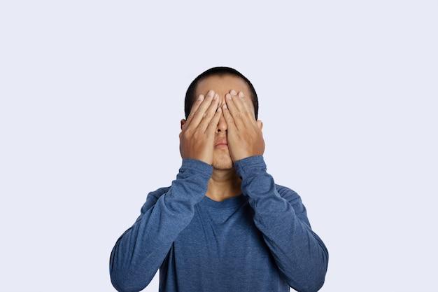 Portret młodzieńca zasłaniając oczy ręcznie na białym tle.