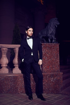 Portret moda elegancki długowłosy młody człowiek. atrakcyjny i przystojny model męski w czarnym garniturze z wąsem na ulicy w nocy