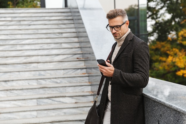Portret moda mężczyzna 30s w okularach, spacerując ulicą miasta i przy użyciu smartfona
