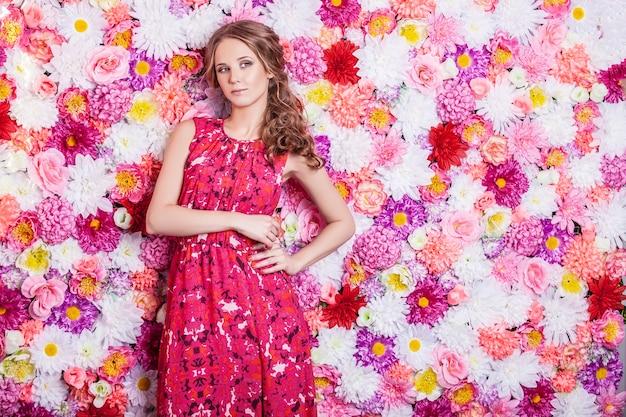 Portret moda piękna kobieta, słodka i zmysłowa z luksusowym makijażem i włosami na tle kolorów kwiatów