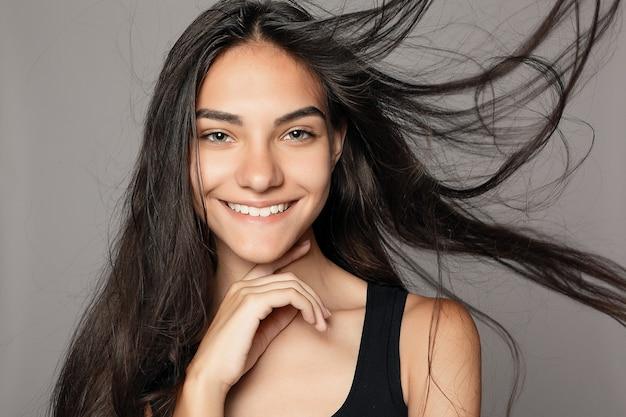 Portret moda uroda młoda piękna brunetka dziewczyna z długie czarne proste włosy latające. wspaniałe włosy. zadymione oczy. modny styl.