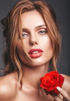 Portret moda uroda model młody blond kobieta z naturalnego makijażu i doskonałej skóry z piękną różą pozowanie