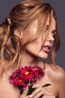 Portret moda uroda model młody blond kobieta z naturalnego makijażu i doskonałej skóry z pozowanie jasne kwiaty
