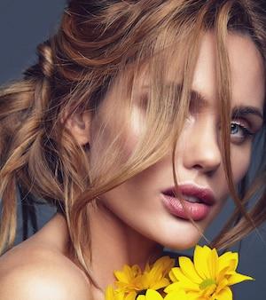 Portret moda uroda model młody blond kobieta z naturalnego makijażu i doskonałej skóry z pozowanie jasny żółty kwiat chryzantemy