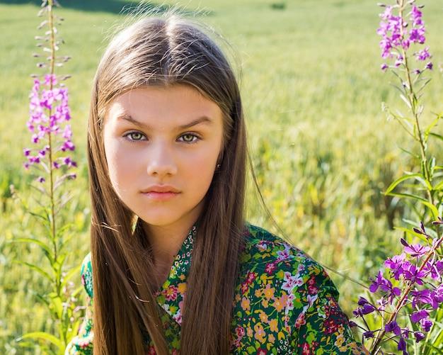 Portret model młoda piękna dziewczyna, która patrząc w kamerę na zielonym kwitnącym trawniku wśród fioletowych kwiatów