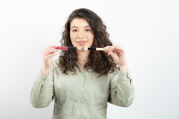 Portret modelka modna dziewczyna trzyma pędzel z szminką na białej ścianie.