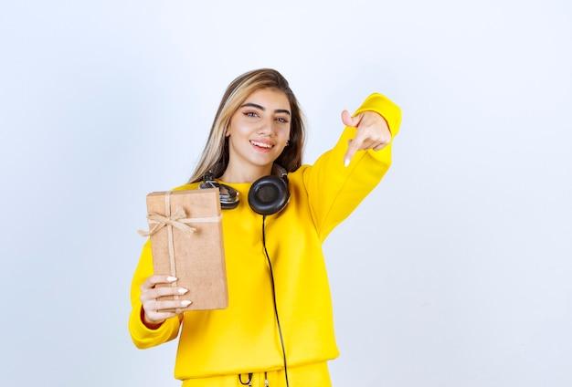 Portret modelki trzymającej papierowe pudełko z kokardą na białym tle nad białą ścianą