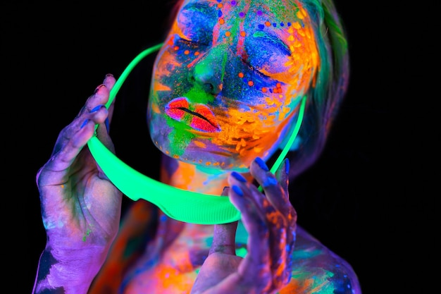 Portret modelki z fluorescencyjnym makijażem pozującym w świetle uv z kolorowym makijażem
