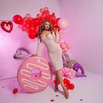Portret modelki z naturalnym makijażem. czerwone i różowe balony na ścianie.
