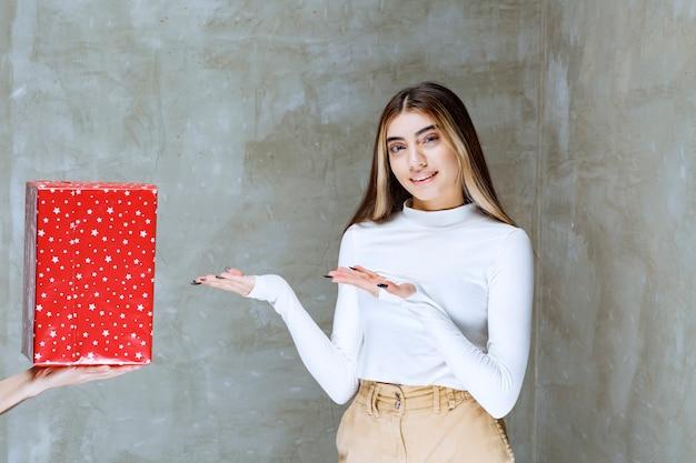 Portret modelu dziewczyny stojącej w pobliżu obecnego pudełka na białym tle nad kamieniem