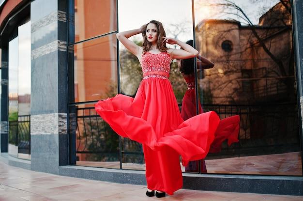 Portret modna dziewczyna przy czerwoną wieczór suknią pozuje tła lustra okno nowożytny budynek. dmuchająca sukienka w powietrzu