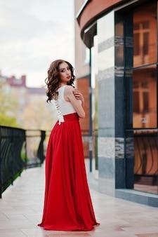 Portret modna dziewczyna przy czerwoną wieczór suknią pozuje tła lustra okno nowożytny budynek