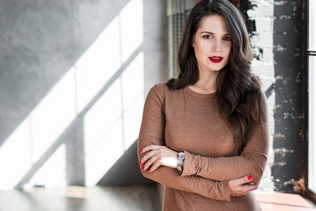 Portret modna młoda kobieta z brunetki długimi włosami patrzeje kamerę
