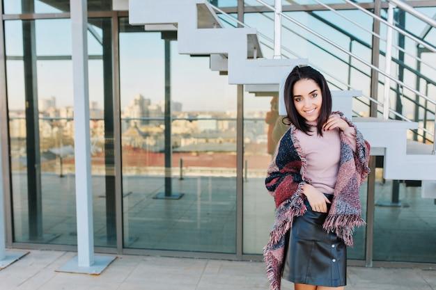 Portret modna uśmiechnięta młoda brunetka kobieta na tarasie w słoneczny dzień na widok na duże miasto. uśmiechnięty w bok, sukces, relaksujący czas, chłodzenie w słońcu.