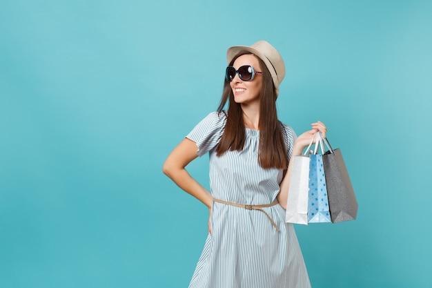 Portret modne atrakcyjna szczęśliwa kobieta w letnią sukienkę, słomkowy kapelusz, okulary przeciwsłoneczne, trzymając pakiety torby z zakupami po zakupach na białym tle na niebieskim tle pastelowych. skopiuj miejsce na reklamę.