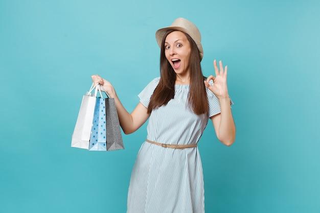 Portret modne uśmiechający się piękny kaukaski kobieta w letnią sukienkę, słomkowy kapelusz, trzymając pakiety torby z zakupami po zakupach na białym tle na niebieskim tle pastelowych. skopiuj miejsce na reklamę.