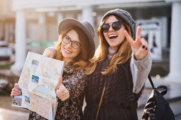Portret modne uśmiechnięte kobiety wyrażające jaskrawe emocje w słoneczny dzień w mieście. szczęśliwe wspólne podróżowanie, cudowne chwile radosnych toutistów, stylowy wygląd, cieszenie się wakacjami, szczęście.