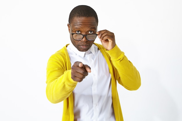 Portret modnego młodego afrykańskiego pracownika lub studenta w białej koszuli i żółtym swetrze, patrząc na swoje okulary, wskazując na aparat z trudnym wyrazem twarzy, wybierając ciebie
