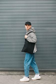 Portret modnego młodego mężczyzny w stroju ulicznym stoi na tle szarej ściany z czarną ekologiczną torbą w ręku