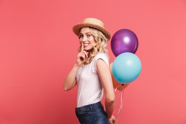 Portret modnej blond kobiety w słomkowym kapeluszu uśmiecha się, trzymając kilka kolorowych balonów izolowanych na różowej ścianie