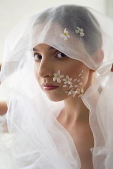 Portret modnej kobiety z białymi kwiatuszkami na twarzy
