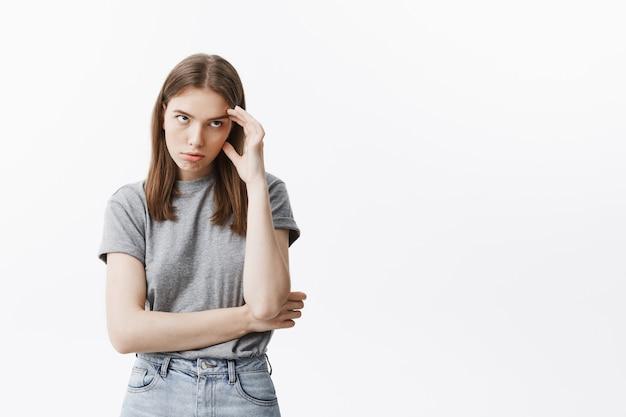 Portret modnej młodej kaukaskiej studenckiej dziewczyny z ciemnymi włosami w modnym stroju masuje czoło ręką, patrząc na bok wkurzony mama uczy jej elementarnych rzeczy.
