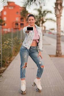 Portret modnej młodej kobiety pozycja na chodniczku pokazuje telefon komórkowego