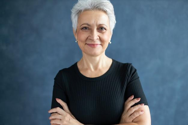 Portret modnej siwowłosej kobiety na emeryturze, pozowanie na białym tle w czarnej koszulce, trzymając ręce skrzyżowane, będąc w dobrym nastroju, patrząc na kamerę z pewnym uśmiechem, wyrażając pozytywne emocje