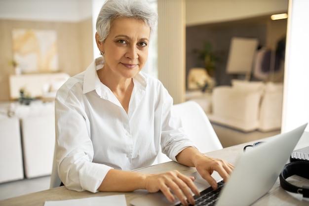 Portret modnej, wesołej 50-letniej pisarki w białej koszuli, która używa do pracy zwykłego elektronicznego gadżetu, wpisując kolejny rozdział swojej nowej książki