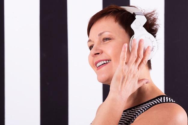 Portret modniś starszej kobiety słuchająca muzyka