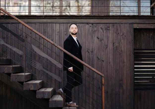 Portret modny dobrze ubrany mężczyzna z brodą pozowanie na zewnątrz