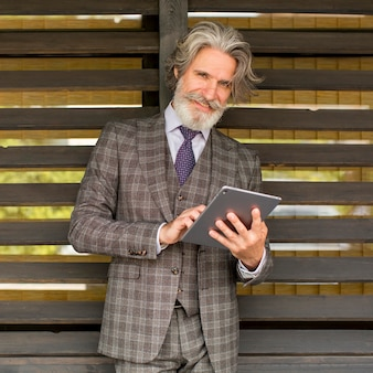 Portret modny dojrzały mężczyzna trzyma tabletkę