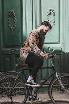 Portret modny młody człowiek jedzie bicykl