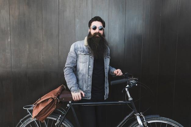 Portret modny młody człowiek jest ubranym okulary przeciwsłonecznych stoi przed czarną drewnianą ścianą z bicyklem