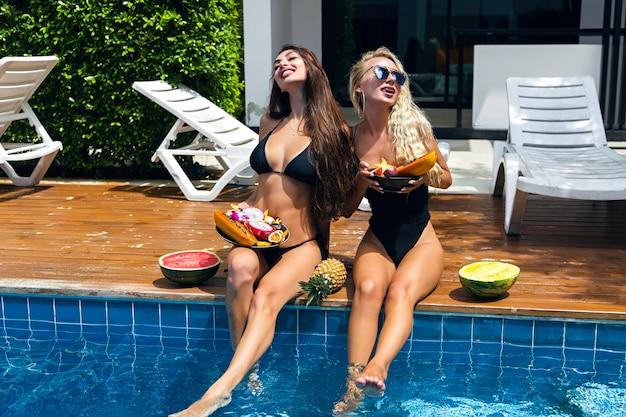 Portret mody na świeżym powietrzu dla dwóch ładnych przyjaciółek, które bawią się przy basenie, trzymają słodkie owoce tropikalne, seksowne bikini, okulary przeciwsłoneczne, zabawa w towarzystwie, opalanie.