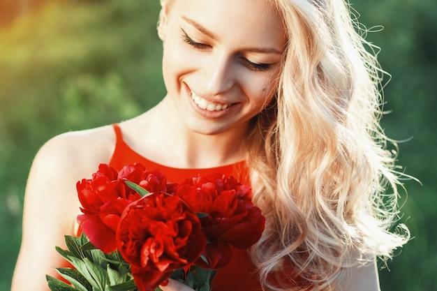 Portret mody piękna uśmiechnięta kobieta z czerwonymi kwiatami