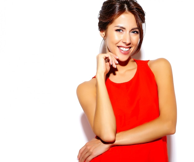Portret mody śliczny młoda kobieta model w czerwonej sukni na białej ścianie
