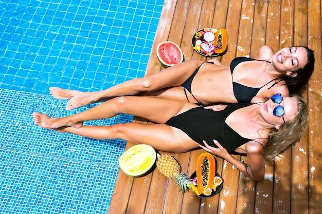 Portret mody w plenerze dla dwóch ładnych przyjaciółek, które bawią się leżąc i relaksując się przy basenie, trzymając słodkie owoce tropikalne, seksowne bikini, okulary przeciwsłoneczne, towarzystwo, opalanie się.