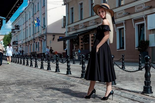 Portret mody wdzięcznej kobiety w eleganckim słomkowym kapeluszu i sukience, która idzie ulicą miasta