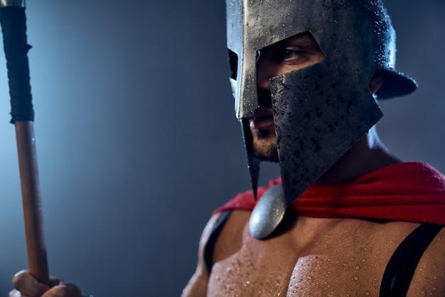Portret mokrego spartańskiego wojownika trzymającego włócznię i odwracającego wzrok. zbliżenie na muskularny mężczyzna w czerwonym płaszczu i kasku z kroplami wody pozowanie w ciemnej atmosferze. starożytna sparta, koncepcja wojownika.