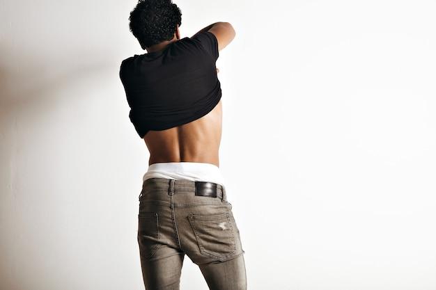 Portret muskularnego młodego modelu z tyłu zdejmującego czarną koszulkę z krótkim rękawem bez etykiety na białej ścianie