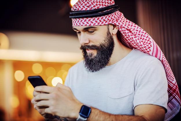 Portret muskularnego przystojnego, brodatego muzułmanina za pomocą swojego smartfona do surfowania w internecie lub odpowiadania na wiadomości w mediach społecznościowych, stojąc w kawiarni.