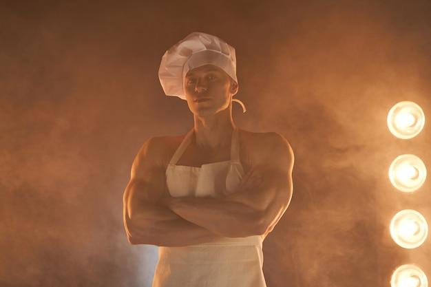 Portret muskularnego szefa kuchni w białym fartuchu i kapeluszu kucharza, pozowanie z założonymi rękoma na zadymionym tle gospodyni domowa. mąż w kuchni. brutalny rzeźnik.