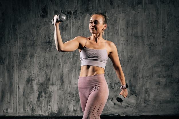 Portret muskularnej młodej kobiety lekkoatletycznego z doskonałego pięknego ciała na sobie odzież sportową robi ćwiczenia z podnoszeniem hantli i odwracając wzrok. kobieta fitness kaukaski pozowanie w studio.