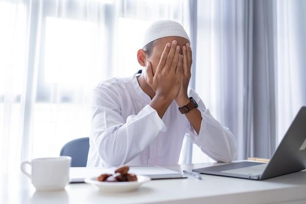 Portret muzułmańskiego mężczyzny stres za pomocą laptopa zakryć twarz ręką podczas pracy w domu