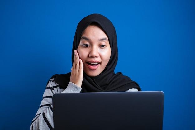 Portret muzułmańskiej bizneswoman noszącej hidżab za pomocą laptopa z gestem zszokowanego oszołomionego wyrazu twarzy, kobieta w biurze